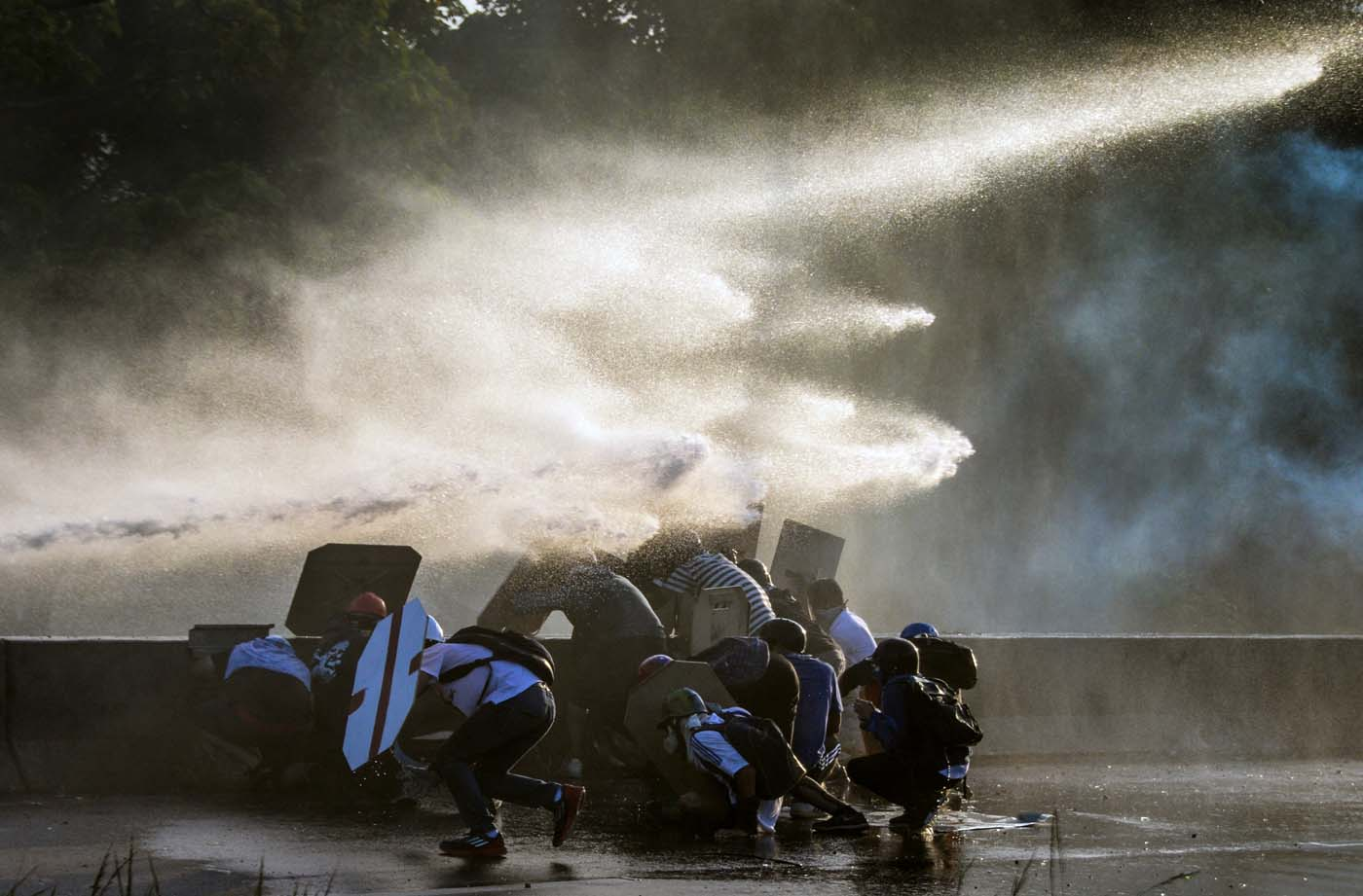 Venezuelan opposition activists clash with the riot police during a rally against the government of President Nicolas Maduro, in Caracas, on May 18, 2017. Venezuelan opposition leader Henrique Capriles said Thursday authorities confiscated his passport and prevented him from travelling to New York to discuss his country's deadly political crisis with United Nations officials. On Monday Venezuelans launched a seventh week of anti-government demonstrations by blocking roads, vowing not to budge all day in protest at a deadly political and economic crisis. / AFP PHOTO / FEDERICO PARRA
