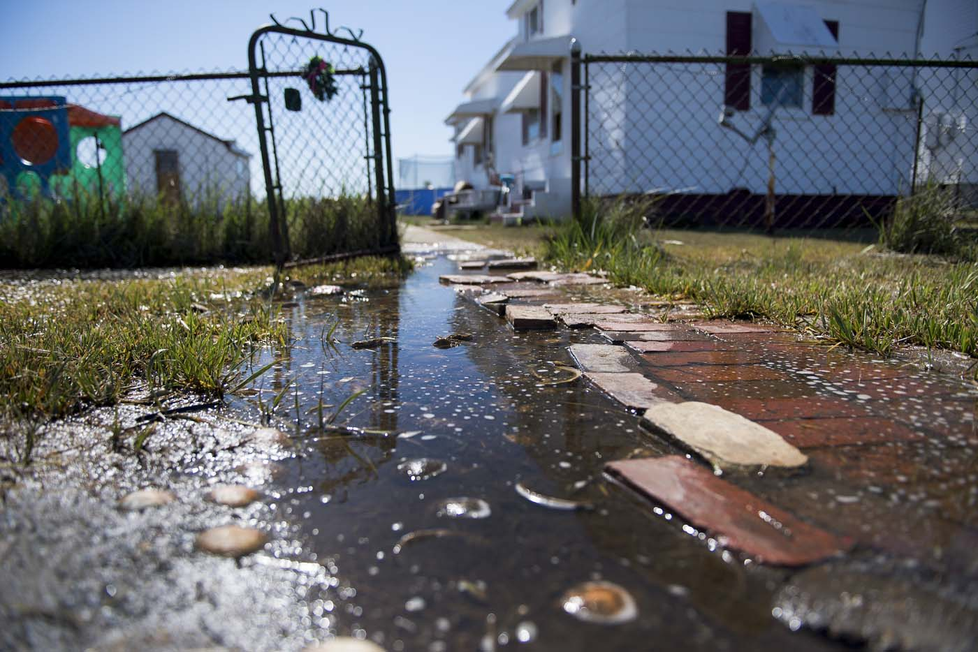 Sea water collects on the front walk way of a home in Tangier, Virginia, May 15, 2017, where climate change and rising sea levels threaten the inhabitants of the slowly sinking island. Now measuring 1.2 square miles, Tangier Island has lost two-thirds of its landmass since 1850. If nothing is done to stop the erosion, it may disappear completely in the next 40 years. / AFP PHOTO / JIM WATSON