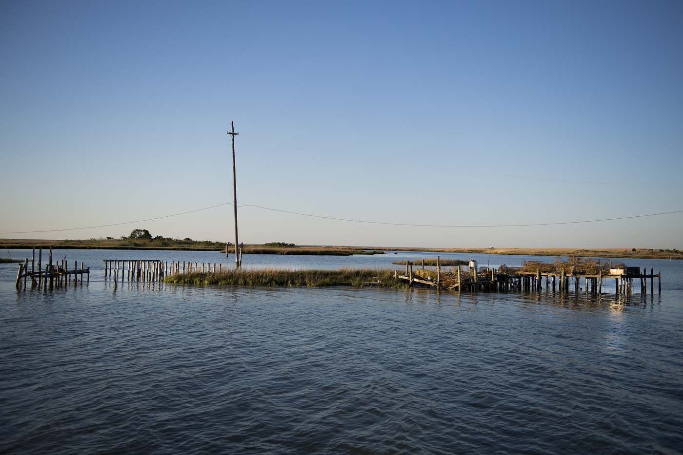 Supports jet out of the water where crab shanties used to stand on a patch of land now surrounded by water in Tangier, Virginia, May 15, 2017, where climate change and rising sea levels threaten the inhabitants of the slowly sinking island. Now measuring 1.2 square miles, Tangier Island has lost two-thirds of its landmass since 1850. If nothing is done to stop the erosion, it may disappear completely in the next 40 years. / AFP PHOTO / JIM WATSON