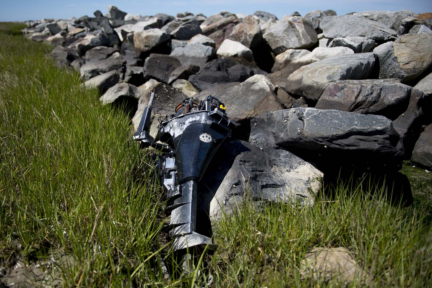 An abandoned outboard boat motor sits against the man-made sea wall that was engineered by the Army Corps of Engineers in 1999 to prevent erosion in Tangier, Virginia, May 15, 2017, where climate change and rising sea levels threaten the inhabitants of the slowly sinking island. Now measuring 1.2 square miles, Tangier Island has lost two-thirds of its landmass since 1850. If nothing is done to stop the erosion, it may disappear completely in the next 40 years. / AFP PHOTO / JIM WATSON