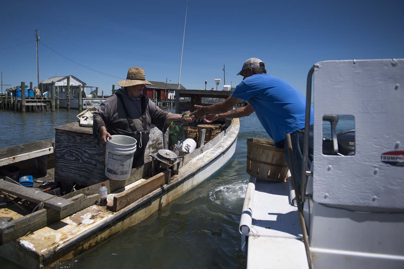 Waterman Tabby Crockett (L) sells his peeler crabs to Mayor and waterman James Eskridge in Tangier, Virginia, May 15, 2017, where climate change and rising sea levels threaten the inhabitants of the slowly sinking island. Now measuring 1.2 square miles, Tangier Island has lost two-thirds of its landmass since 1850. If nothing is done to stop the erosion, it may disappear completely in the next 40 years. / AFP PHOTO / JIM WATSON