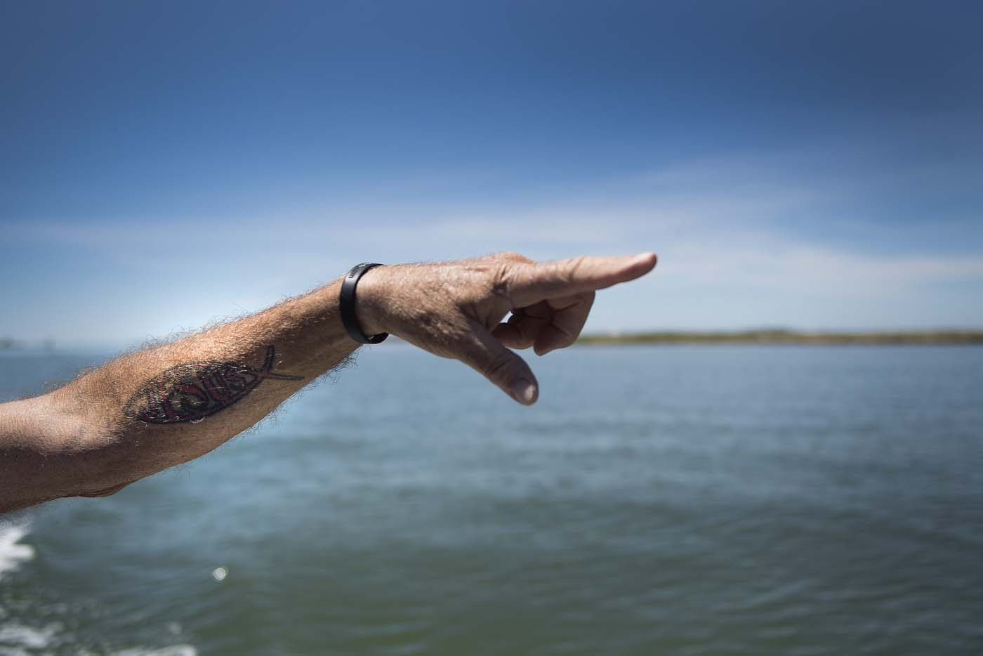 Mayor and waterman James Eskridge's tattoo of the Jesus fish adorns his arm as he points out areas that have been completely eroded away in Tangier, Virginia, May 16, 2017, where climate change and rising sea levels threaten the inhabitants of the slowly sinking island. Now measuring 1.2 square miles, Tangier Island has lost two-thirds of its landmass since 1850. If nothing is done to stop the erosion, it may disappear completely in the next 40 years. / AFP PHOTO / JIM WATSON