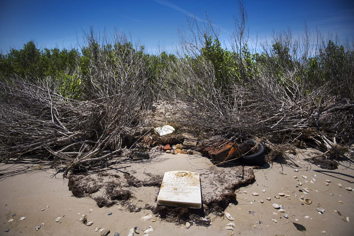 A grave stone rests on the beach where a cemetery once stood but has been washed away due to erosion in an area called Canaan in Tangier, Virginia, May 16, 2017, where climate change and rising sea levels threaten the inhabitants of the slowly sinking island. Now measuring 1.2 square miles, Tangier Island has lost two-thirds of its landmass since 1850. If nothing is done to stop the erosion, it may disappear completely in the next 40 years. / AFP PHOTO / JIM WATSON