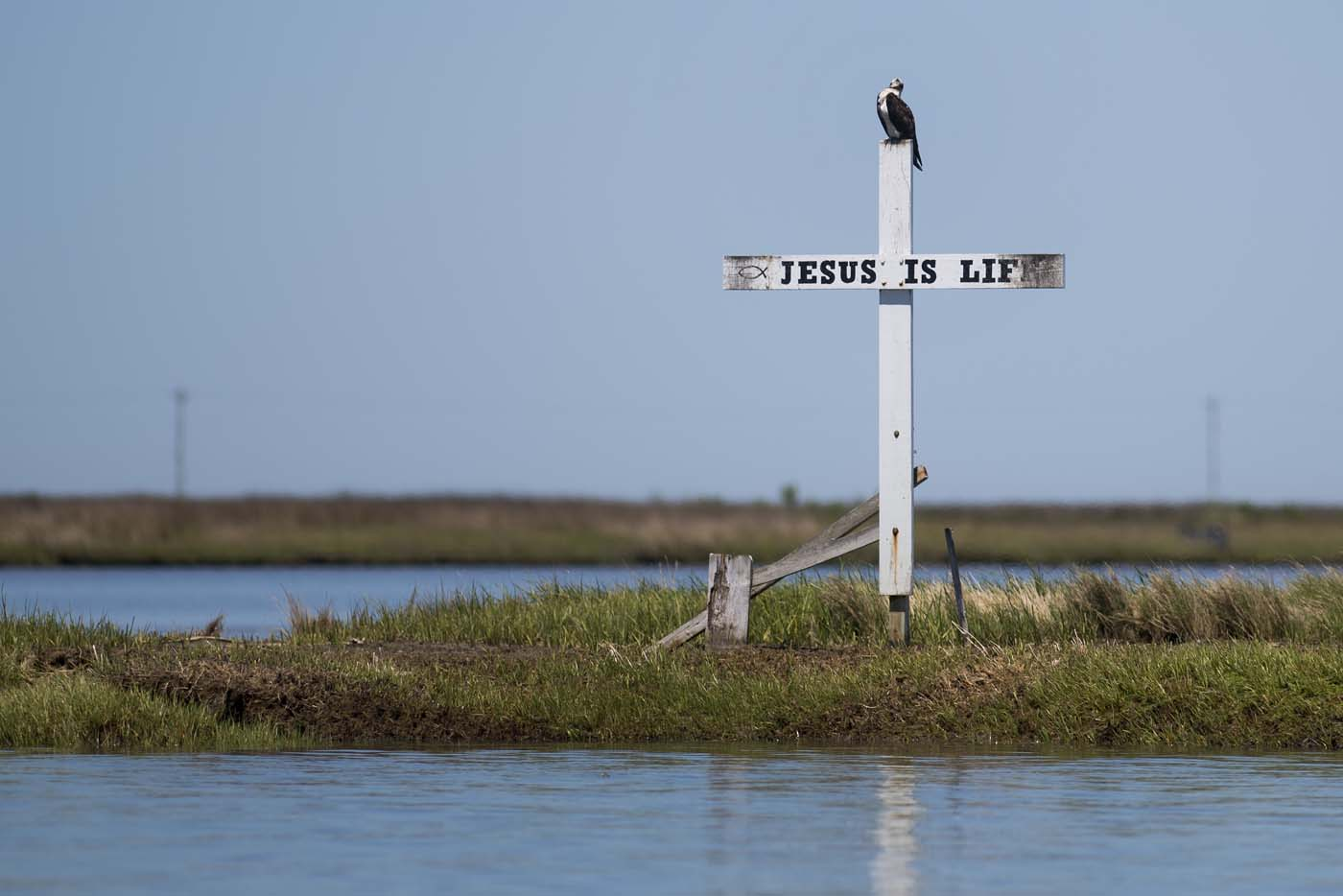 "A cross stands at the mouth of the harbor reading ""Jesus is Life"" in Tangier, Virginia, May 16, 2017, where climate change and rising sea levels threaten the inhabitants of the slowly sinking island. Now measuring 1.2 square miles, Tangier Island has lost two-thirds of its landmass since 1850. If nothing is done to stop the erosion, it may disappear completely in the next 40 years. / AFP PHOTO / JIM WATSON"
