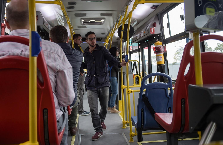 """592/5000 El venezolano Jairo Suescun, de 30 años, viaja en autobús durante una entrevista con la AFP en Bogotá, Colombia, el 24 de mayo de 2017. Suescun abandonó su ciudad natal de San Cristóbal hace cinco meses para Colombia, ya que su madre era nacional colombiana. Miles de venezolanos han abandonado su país para escapar de las dificultades y la violencia de su crisis económica y política. De Brasil a Estados Unidos a Europa, aquí hay cinco caras y voces de estos venezolanos que se han exiliado en los últimos dos años. / AFP PHOTO / RAUL ARBOLEDA / IR CON LA HISTORIA AFP """"Los venezolanos en el exilio: cinco caras de la crisis"""""""