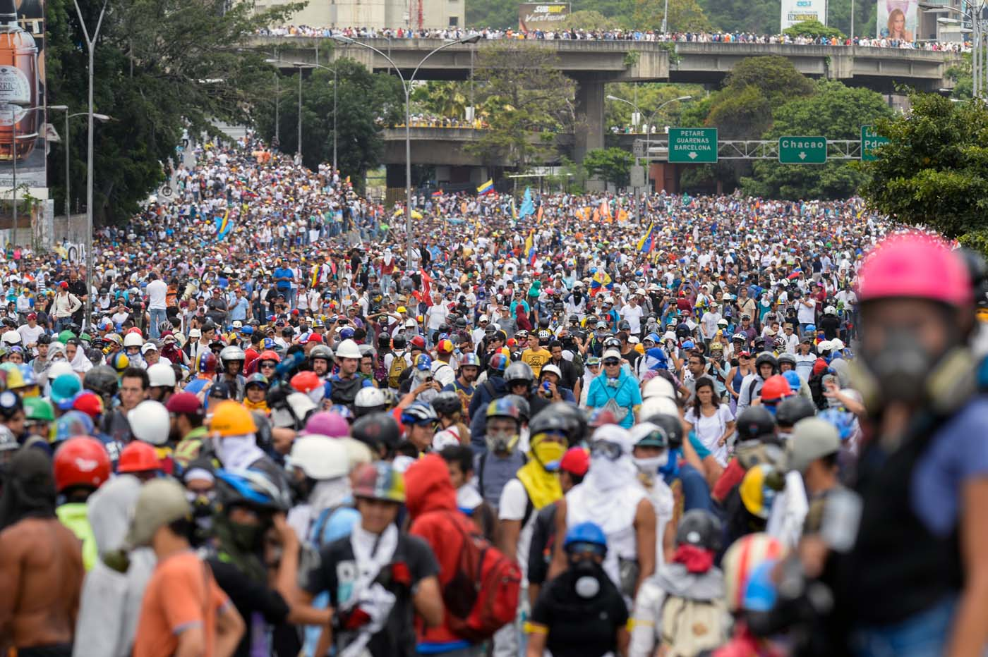 "Opposition activists march during a protest against the government of President Nicolas Maduro in Caracas on May 31, 2017.  Venezuelan authorities on Wednesday began signing up candidates for a planned constitutional reform body, a move that has inflamed deadly unrest stemming from anti-government protests. Opponents of socialist President Nicolas Maduro say he aims to keep himself in power by stacking the planned ""constituent assembly"" with his allies.  / AFP PHOTO / FEDERICO PARRA"