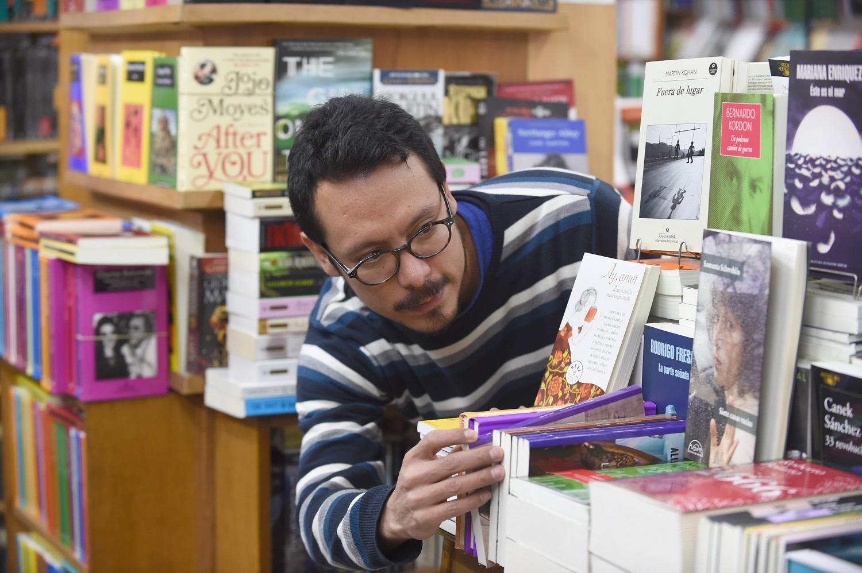 """El venezolano Jairo Rojas, de 36 años, trabaja en una librería en Montevideo el 31 de mayo de 2017. Rojas se trasladó en abril de 2015 a Uruguay, donde publicó tres libros de poesía, ganó premios de poesía y lanzó una operación de publicación de versos con sus amigos. Miles de venezolanos han abandonado su país para escapar de las dificultades y la violencia de su crisis económica y política. De Brasil a Estados Unidos a Europa, aquí hay cinco caras y voces de estos venezolanos que se han exiliado en los últimos dos años. / AFP PHOTO / MIGUEL ROJO / PARA IR CON LA HISTORIA AFP """"Los venezolanos en el exilio: cinco caras de la crisis"""""""