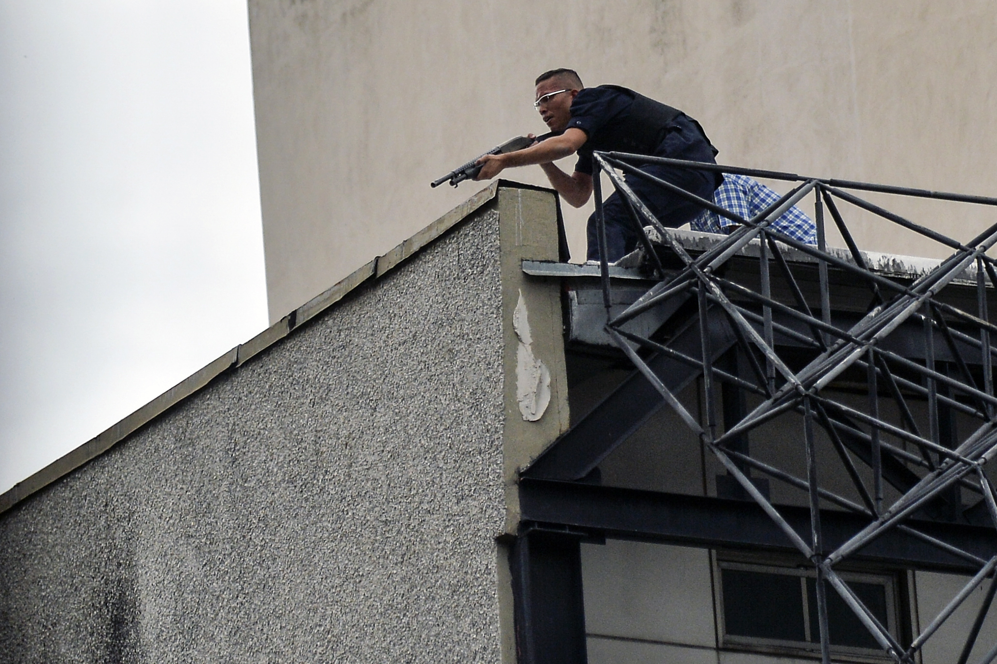 "A man aims his weapon at demonstrators as they attack the administration headquarters of the Supreme Justice Court during riots following a protests against President Nicolas Maduro's government in Caracas, Venezuela, on June 7, 2017. The head of the Venezuelan military, General Vladimir Padrino Lopez, who is also President Nicolas Maduro's defence minister, is warning his troops not to commit ""atrocities"" against protesters demonstrating in the country's deadly political crisis. Tuesday's warning came after more than two months of violent clashes between protesters and security forces. The opposition and a press rights group say security forces have run over, attacked and robbed protesters and journalists. / AFP PHOTO / LUIS ROBAYO"
