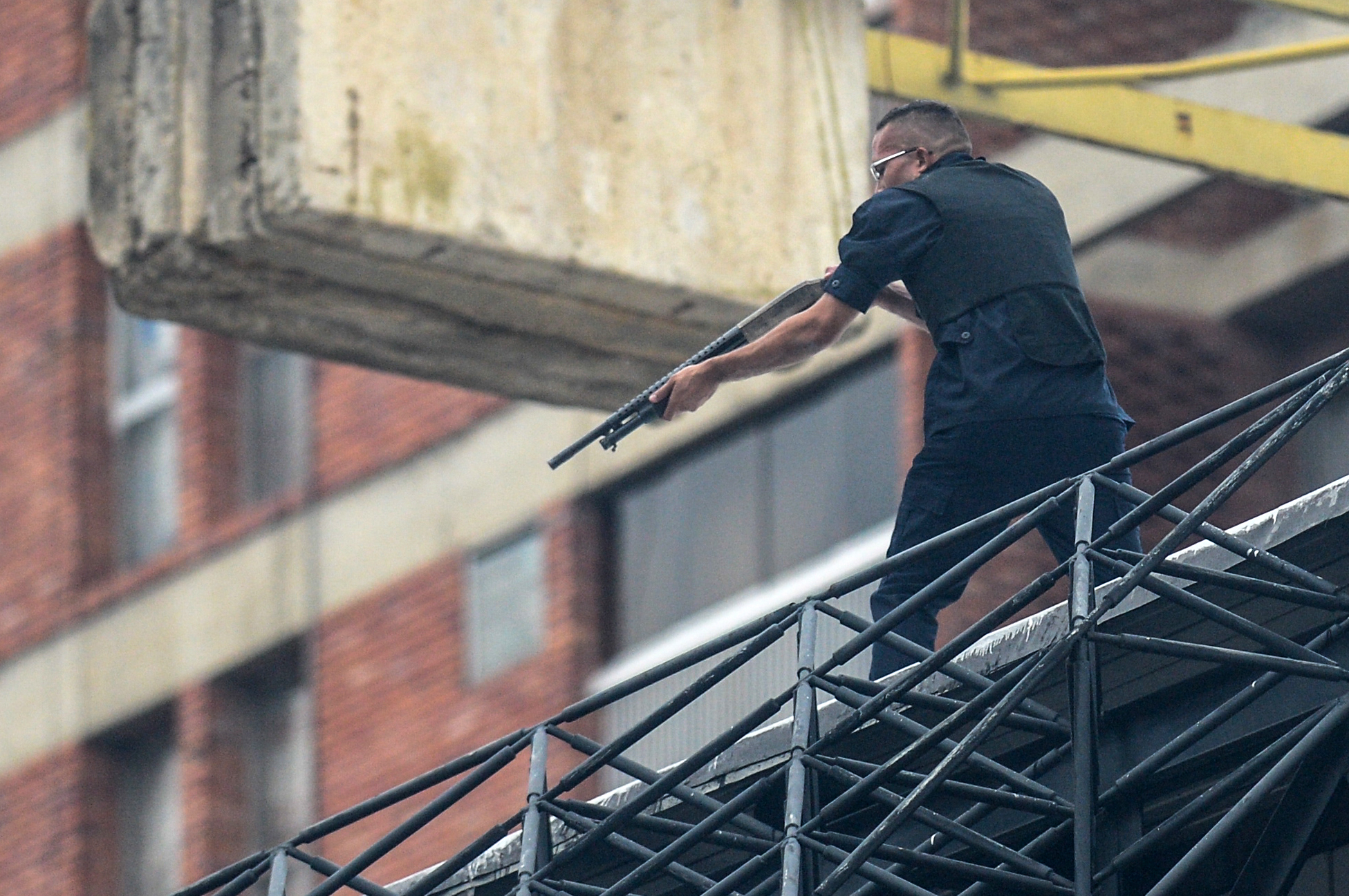 "A man aims his weapon at demonstrators as they attack the administration headquarters of the Supreme Justice Court during riots following a protests against President Nicolas Maduro's government in Caracas, Venezuela, on June 7, 2017. The head of the Venezuelan military, General Vladimir Padrino Lopez, who is also President Nicolas Maduro's defence minister, is warning his troops not to commit ""atrocities"" against protesters demonstrating in the country's deadly political crisis. Tuesday's warning came after more than two months of violent clashes between protesters and security forces. The opposition and a press rights group say security forces have run over, attacked and robbed protesters and journalists. / AFP PHOTO / FEDERICO PARRA"