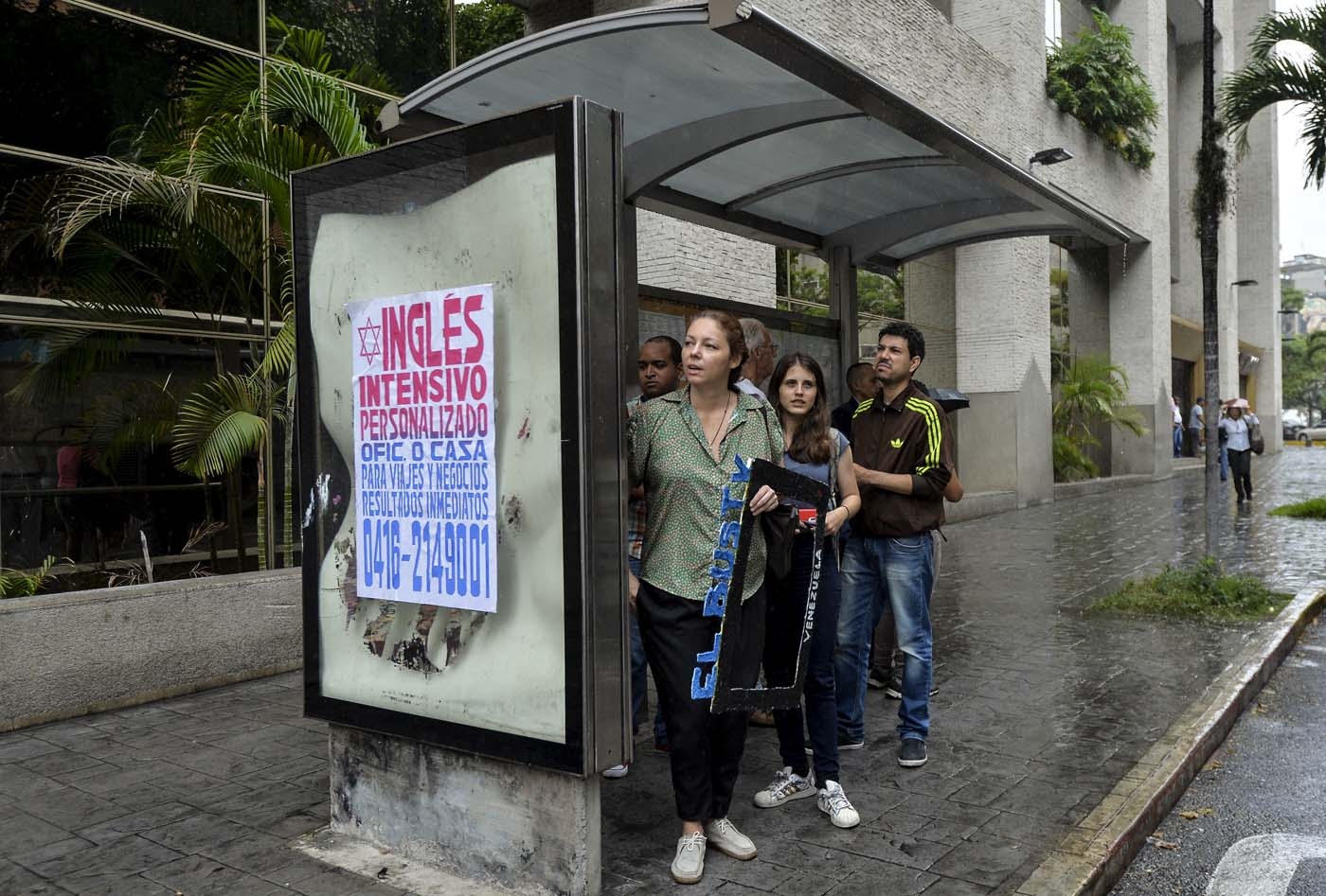 Laura Castillo (L), Abril Mejias (C) and Dereck Blanco wait for a bus to give an on-board presentation of the Bus TV news in Caracas, Venezuela, on June 6, 2017. A group of young Venezuelan reporters board buses to present the news, as part of a project to keep people informed in the face of what the opposition and the national journalists' union describe as censorship by the government of Nicolas Maduro. / AFP PHOTO / LUIS ROBAYO