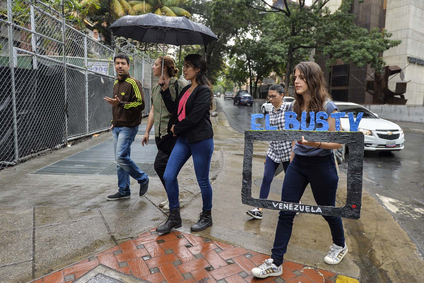 Dereck Blanco (L), Laura Castillo (C-1), Maria Gabriela Fernandez (C-2) and Abril Mejias (R) walk to a bus stop to give an on-board presentation of the Bus TV news in Caracas, Venezuela, on June 6, 2017. A group of young Venezuelan reporters board buses to present the news, as part of a project to keep people informed in the face of what the opposition and the national journalists' union describe as censorship by the government of Nicolas Maduro. / AFP PHOTO / LUIS ROBAYO
