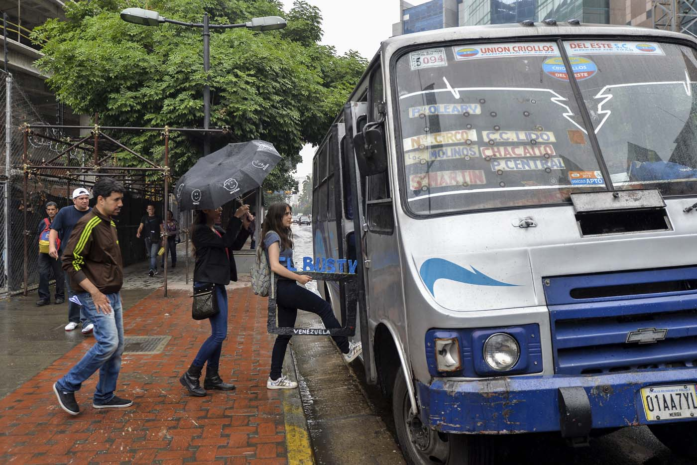 Dereck Blanco (L), Maria Gabriela Fernandez (C) and Abril Mejias board a bus to give a presentation of the Bus TV news in Caracas, Venezuela, on June 6, 2017. A group of young Venezuelan reporters board buses to present the news, as part of a project to keep people informed in the face of what the opposition and the national journalists' union describe as censorship by the government of Nicolas Maduro. / AFP PHOTO / LUIS ROBAYO