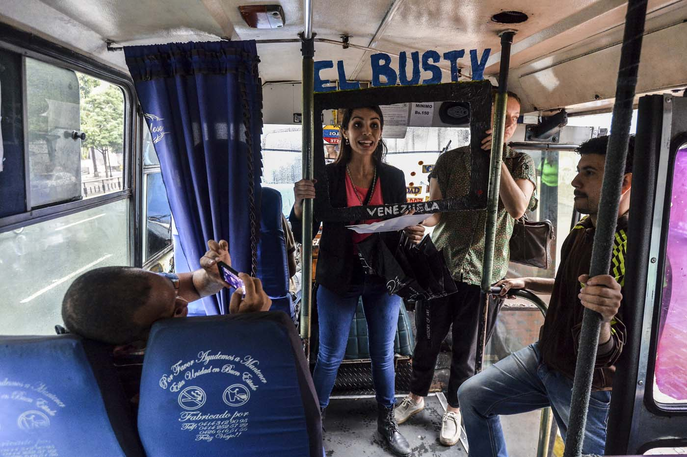 Maria Gabriela Fernandez (C) gives a presentation of the Bus TV news in Caracas, Venezuela, on June 6, 2017. A group of young Venezuelan reporters board buses to present the news, as part of a project to keep people informed in the face of what the opposition and the national journalists' union describe as censorship by the government of Nicolas Maduro. / AFP PHOTO / LUIS ROBAYO