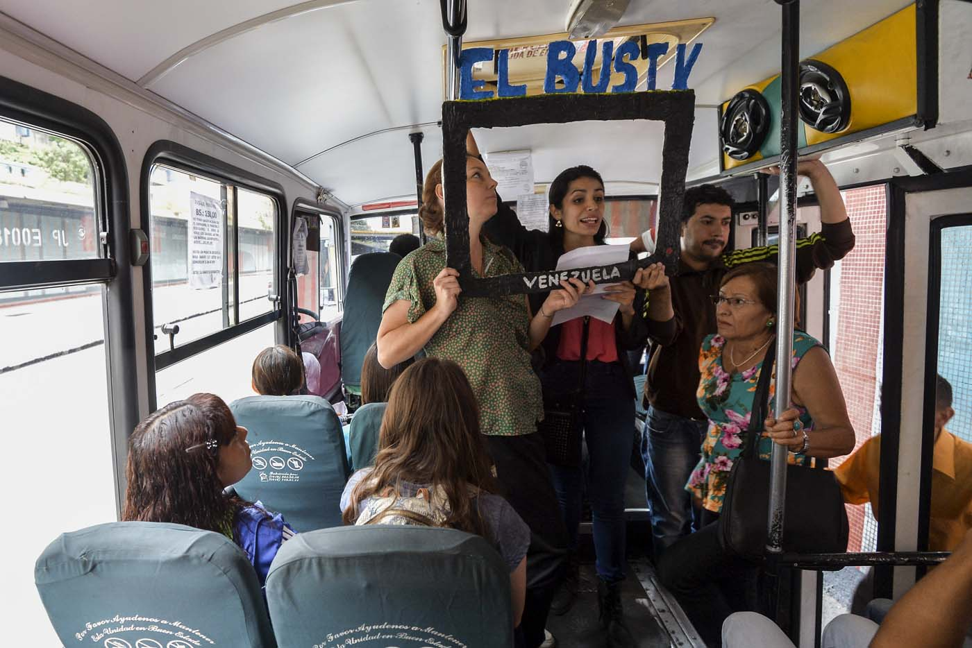 Laura Castillo (L), Maria Gabriela Fernandez (C) and Dereck Blanco (R) give a presentation of the Bus TV news in Caracas, Venezuela, on June 6, 2017. A group of young Venezuelan reporters board buses to present the news, as part of a project to keep people informed in the face of what the opposition and the national journalists' union describe as censorship by the government of Nicolas Maduro. / AFP PHOTO / LUIS ROBAYO