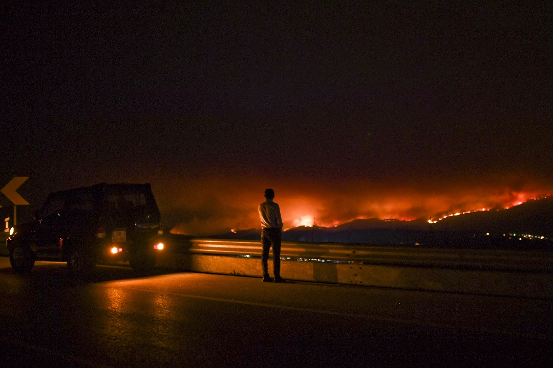 A man stands on the roadside watching a wildfire at Anciao, Leiria, central Portugal, on June 18, 2017. A wildfire in central Portugal killed at least 25 people and injured 16 others, most of them burning to death in their cars, the government said on June 18, 2017. Several hundred firefighters and 160 vehicles were dispatched late on June 17 to tackle the blaze, which broke out in the afternoon in the municipality of Pedrogao Grande before spreading fast across several fronts. / AFP PHOTO / PATRICIA DE MELO MOREIRA