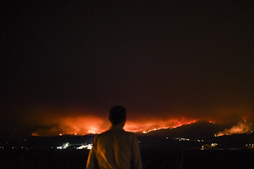 A man stands on the roadside and watches a wildfire at Anciao, Leiria, central Portugal, on June 18, 2017. A wildfire in central Portugal killed at least 25 people and injured 16 others, most of them burning to death in their cars, the government said on June 18, 2017. Several hundred firefighters and 160 vehicles were dispatched late on June 17 to tackle the blaze, which broke out in the afternoon in the municipality of Pedrogao Grande before spreading fast across several fronts. / AFP PHOTO / Patricia De Melo MOREIRA