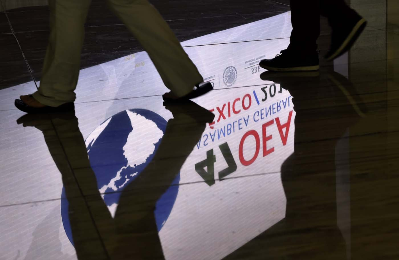 A screen displaying the logo of the 47th General Assembly of the Organization of American States (OAS) is reflected on the floor as people walk by, in the Mexican resort city of Cancun, on June 18, 2017. Foreign ministers from the OAS discuss taking action on the crisis in Venezuela -- a meeting that has infuriated President Nicolas Maduro's government -- ahead of the regional group's general assembly, which runs from Monday through Wednesday. / AFP PHOTO / Pedro PARDO