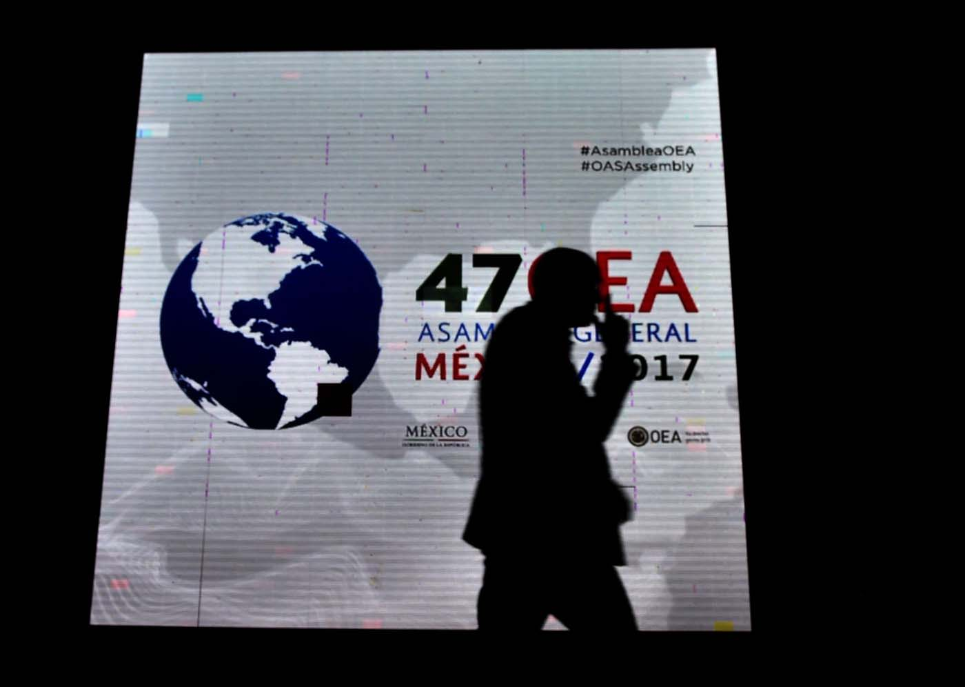 A man passes by a screen displaying the logo of the 47th General Assembly of the Organization of American States (OAS) in the Mexican resort city of Cancun, on June 18, 2017. Foreign ministers from the OAS discuss taking action on the crisis in Venezuela -- a meeting that has infuriated President Nicolas Maduro's government -- ahead of the regional group's general assembly, which runs from Monday through Wednesday. / AFP PHOTO / Pedro PARDO