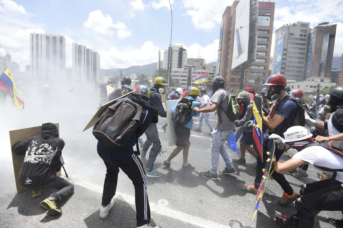 Opposition activists clash with riot police whilst protesting against the government of President Nicolas Maduro along the Francisco Fajardo motorway in Caracas on June 19, 2017. Venezuela's Supreme Court on Friday rejected a bid to put on trial several senior judges accused of favoring embattled President Nicolas Maduro as he clings to power in the face of deadly unrest. / AFP PHOTO / JUAN BARRETO