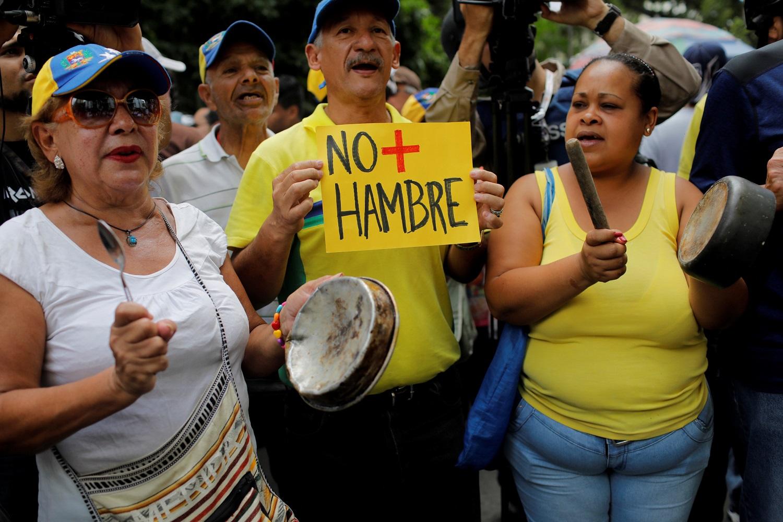 """Los partidarios de la oposición que sostienen macetas y un cartel que dice: """"no más hambrientos"""" asisten a la """"marcha de las ollas vacías"""" contra el gobierno del presidente venezolano Nicolás Maduro en Caracas, Venezuela, June 3, 2017.  REUTERS/Marco Bello"""