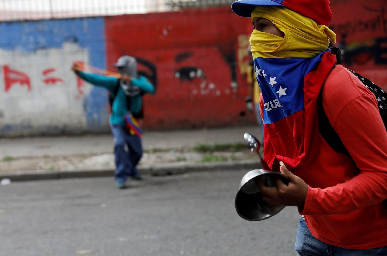 """Un manifestante sostiene una olla mientras asiste a la """"marcha de las ollas vacías"""" contra el gobierno del presidente venezolano Nicolás Maduro. Caracas, Venezuela, June 3, 2017. REUTERS/Carlos Garcia Rawlins"""