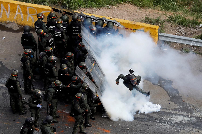 """Imagen de archivo de un miembro de las fuerzas de seguridad antidisturbios pateando una lata de gas lacrimógeno durante las protestas en en Caracas, Venezuela. 29 de mayo 2017. Las fuerzas de seguridad de Venezuela arrestaron al menos a 14 militares bajo sospecha de """"rebelión"""" y """"traición"""" a principios de abril, en la primera semana de protestas contra el Gobierno del presidente Nicolás Maduro, según documentos obtenidos por Reuters. REUTERS/Carlos Garcia Rawlins/File Photo"""