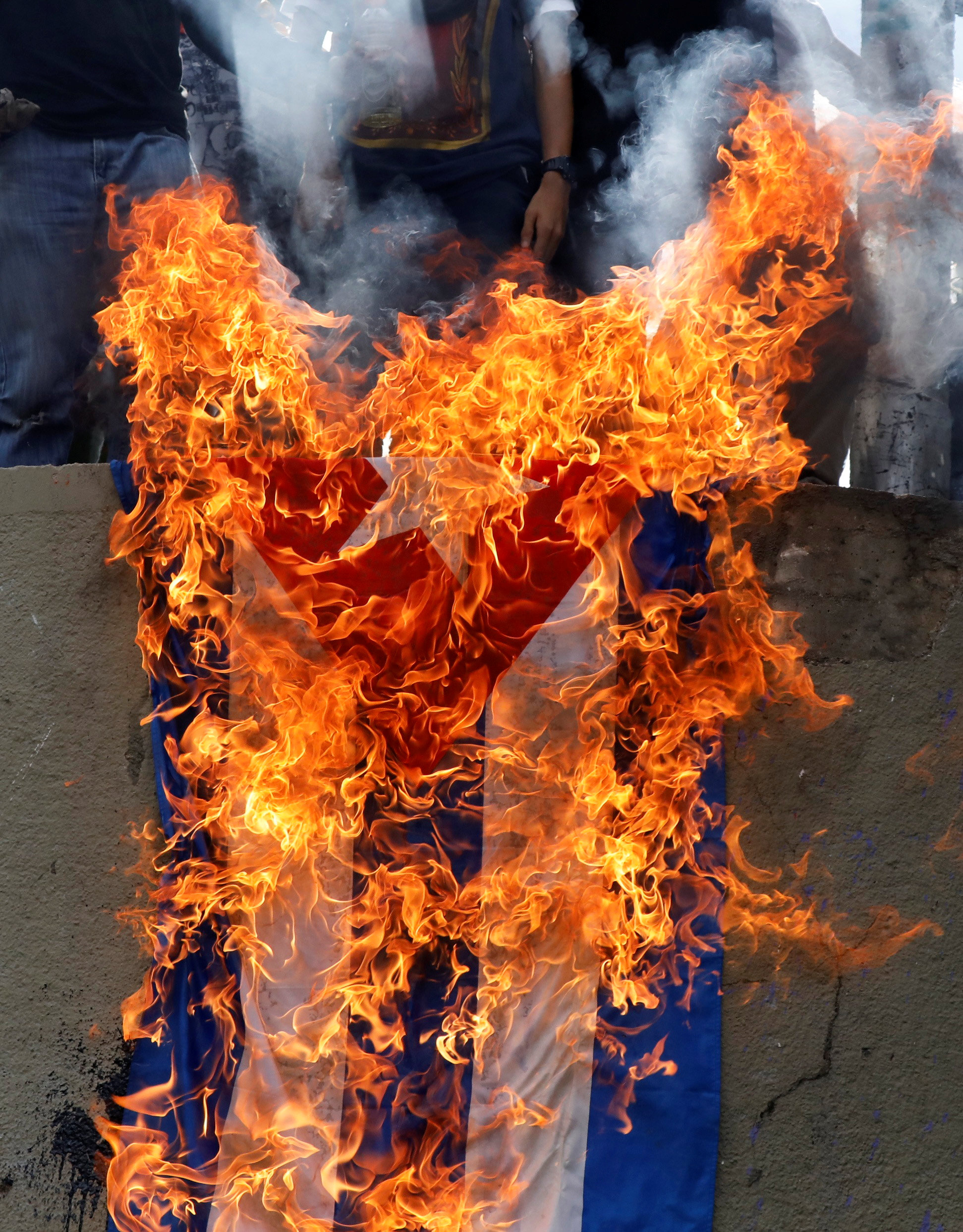 Demonstrators burn a Cuban flag while rallying against Venezuela's President Nicolas Maduro in Caracas, Venezuela, June 10, 2017. REUTERS/Carlos Garcia Rawlins