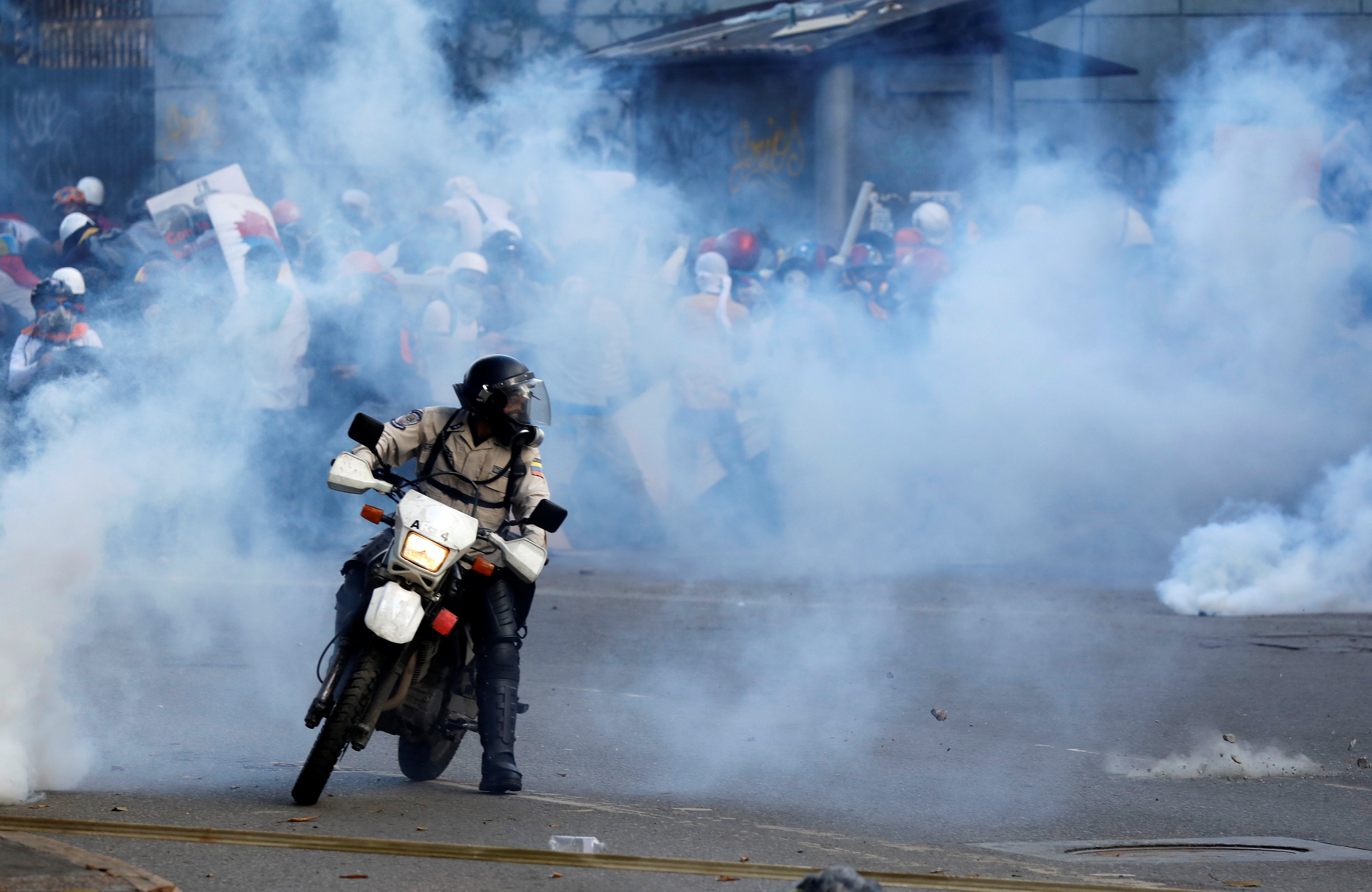 A riot security forces member rides his motorcycle as demonstrators clash with riot security forces while rallying against Venezuela's President Nicolas Maduro in Caracas, Venezuela, June 10, 2017. REUTERS/Carlos Garcia Rawlins