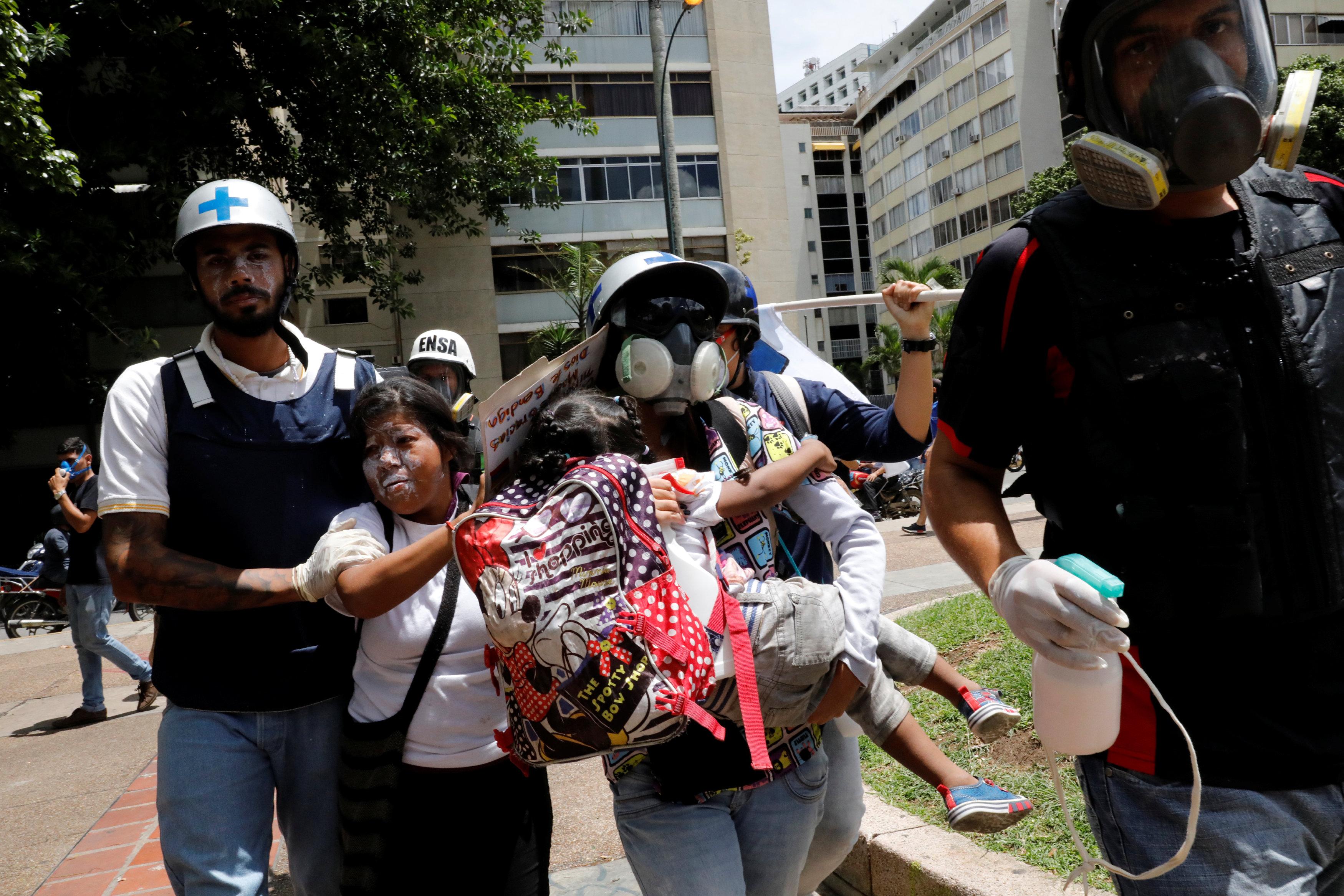 Voluntarios paramédicos rescatan a uno de los menores que resultaron afectados por los gases lacrimógenos en Altamira. REUTERS/Carlos Garcia Rawlins