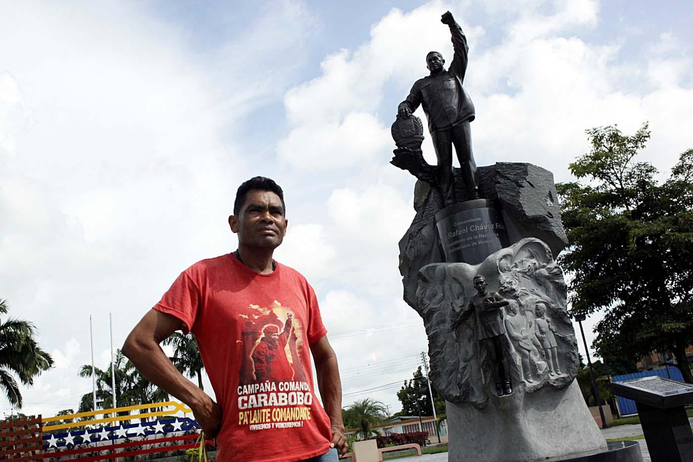 Denny Frias poses for a picture in front of a statue of Venezuela's late President Hugo Chavez in Sabaneta, Venezuela June 13, 2017. Picture taken June 13, 2017. REUTERS/Carlos Eduardo Ramirez