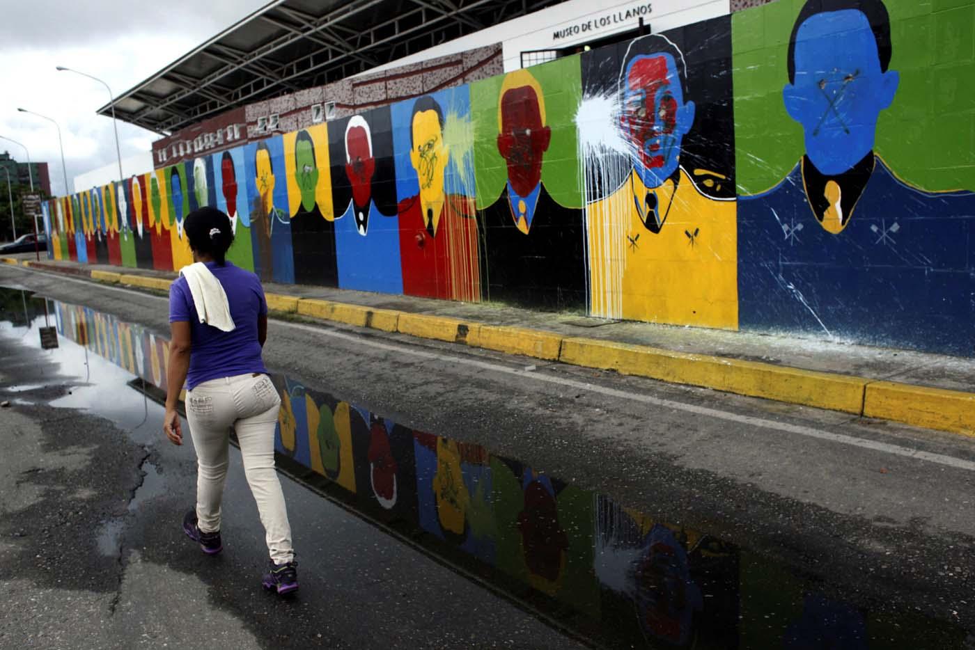 A woman walks next to a mural depicting Venezuela's late President Hugo Chavez in Barinas, Venezuela June 14, 2017. Picture taken June 14, 2017. REUTERS/Carlos Eduardo Ramirez