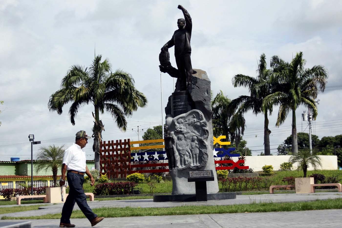 A man walks next to a statue of Venezuela's late President Hugo Chavez in Sabaneta, Venezuela June 13, 2017. Picture taken June 13, 2017. REUTERS/Carlos Eduardo Ramirez