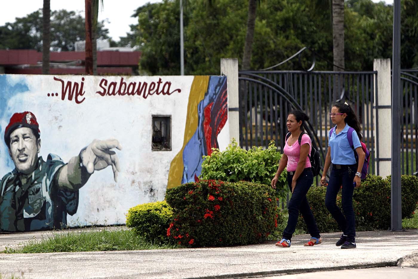 People walk past a mural depicting Venezuela's late President Hugo Chavez in Sabaneta, Venezuela June 13, 2017. Picture taken June 13, 2017. REUTERS/Carlos Eduardo Ramirez