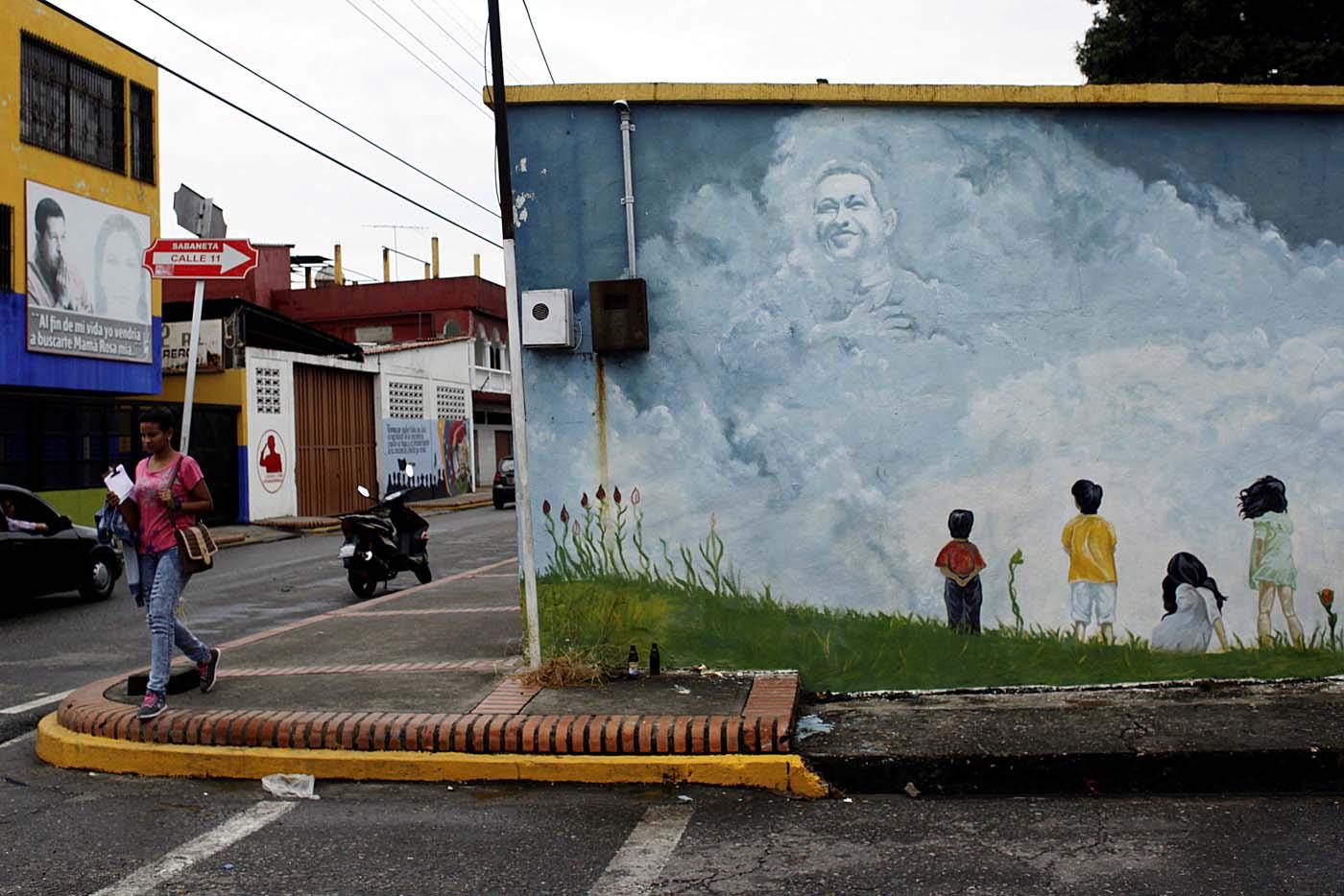 A woman walks past a mural depicting Venezuela's late President Hugo Chavez in Sabaneta, Venezuela June 13, 2017. Picture taken June 13, 2017. REUTERS/Carlos Eduardo Ramirez