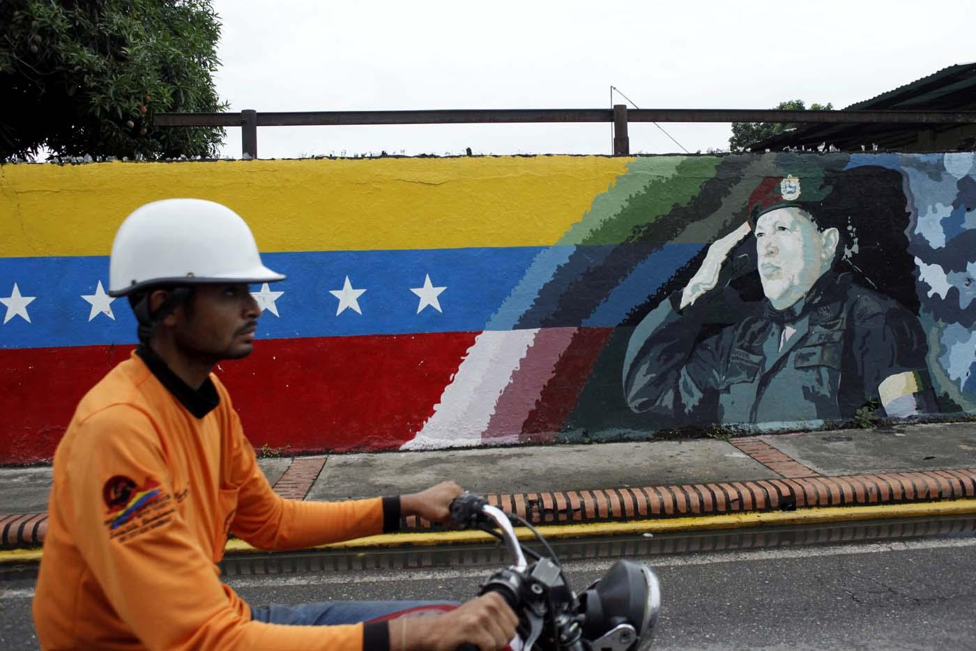 A motorcyclist rides past a mural depicting Venezuela's late President Hugo Chavez in Sabaneta, Venezuela June 13, 2017. Picture taken June 13, 2017. REUTERS/Carlos Eduardo Ramirez
