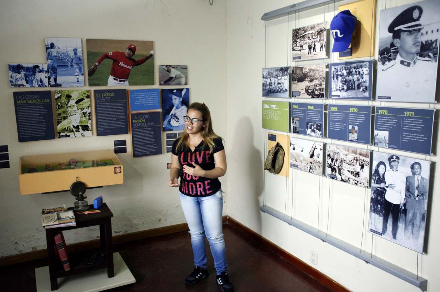 A tour guide talks to people next to pictures of Venezuela's late President Hugo Chavez in his childhood home in Sabaneta, Venezuela June 13, 2017. Picture taken June 13, 2017. REUTERS/Carlos Eduardo Ramirez