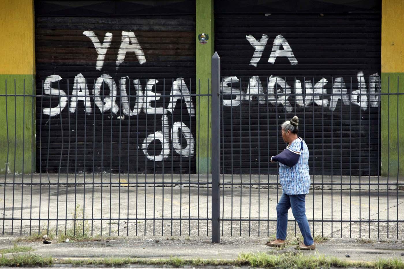 "A woman walks past the gates of a shop that read, ""Already looted"" in Barinas, Venezuela June 12, 2017. Picture taken June 12, 2017. REUTERS/Carlos Eduardo Ramirez"