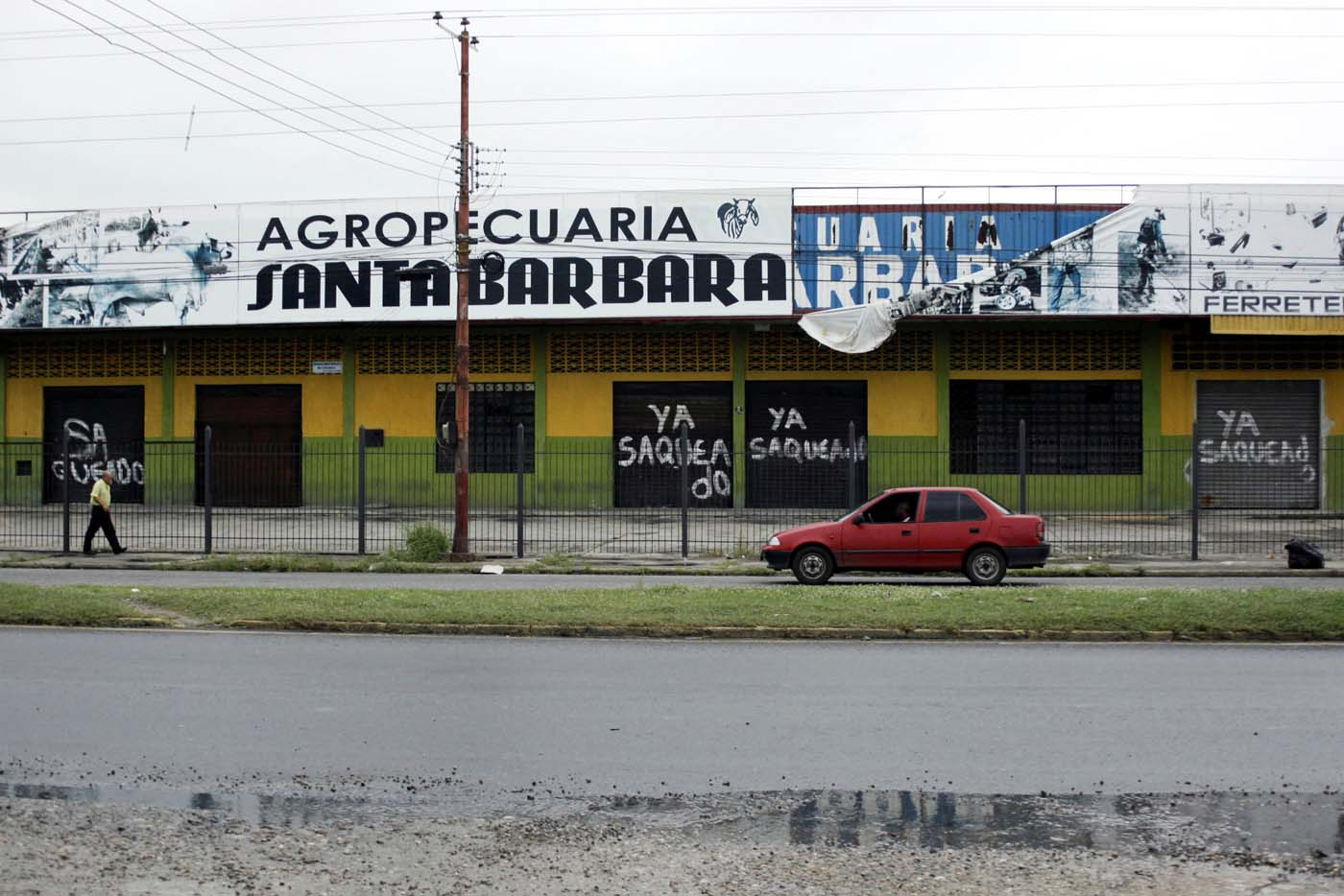 "A man walks past the gates of shops that read, ""Already looted"" in Barinas, Venezuela June 12, 2017. Picture taken June 12, 2017. REUTERS/Carlos Eduardo Ramirez"