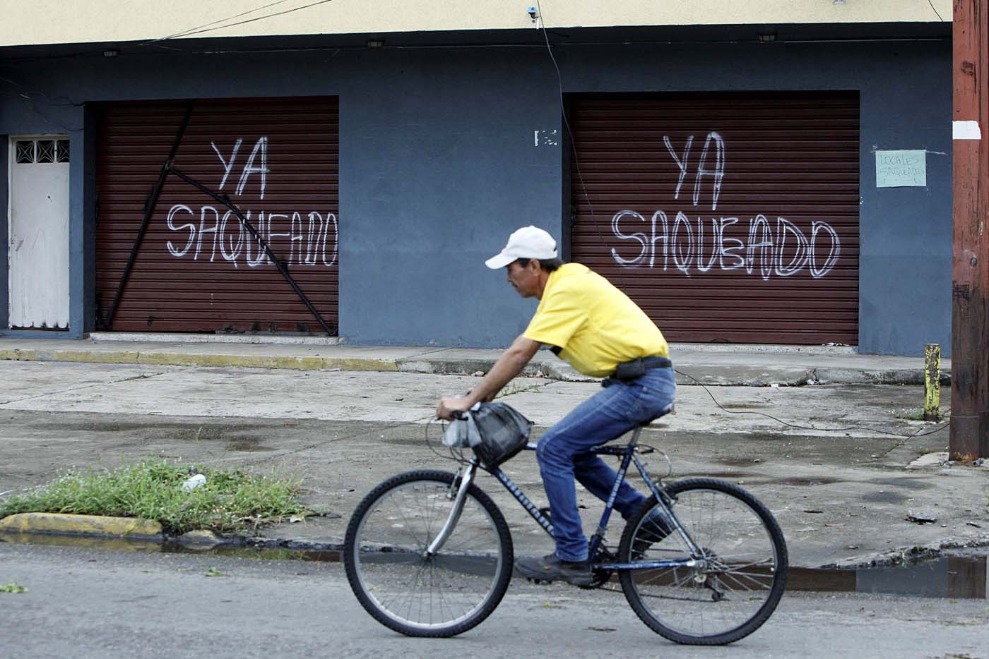 """A man rides a bicycle in front of the gates of a shop that read, """"Already looted"""" in Barinas, Venezuela June 12, 2017. Picture taken June 12, 2017. REUTERS/Carlos Eduardo Ramirez"""
