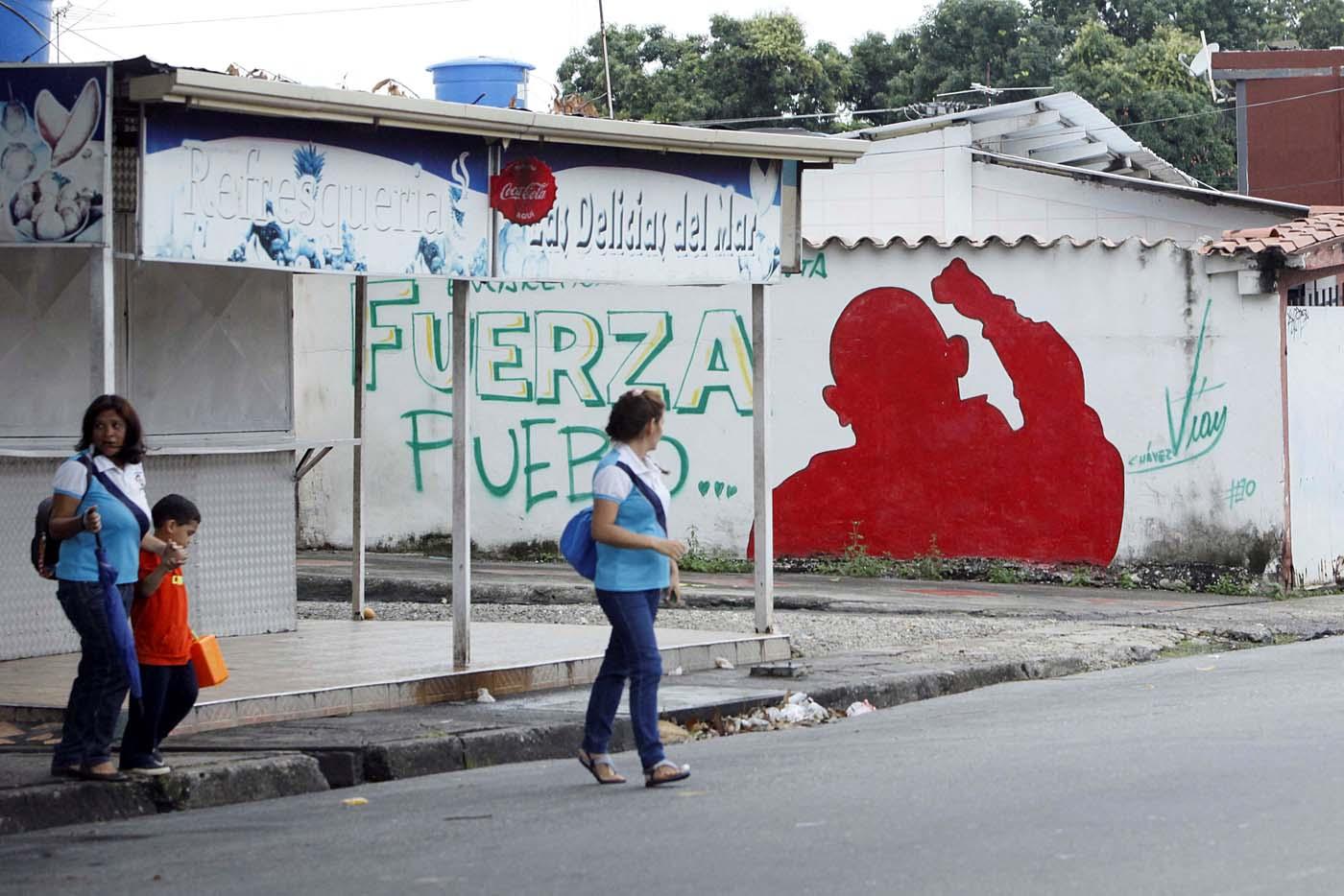 "People walk past a mural depicting Venezuela's late President Hugo Chavez that reads, ""Strength, people"" in Barinas, Venezuela June 12, 2017. Picture taken June 12, 2017. REUTERS/Carlos Eduardo Ramirez"