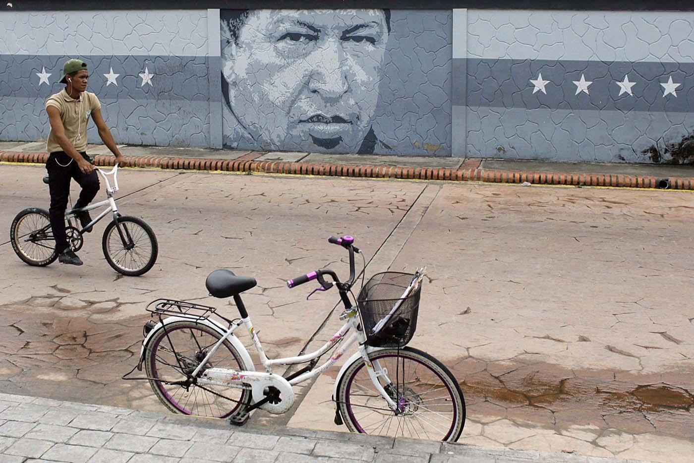 A man rides a bicycle in front a mural depicting Venezuela's late President Hugo Chavez in Sabaneta, Venezuela June 13, 2017. Picture taken June 13, 2017. REUTERS/Carlos Eduardo Ramirez