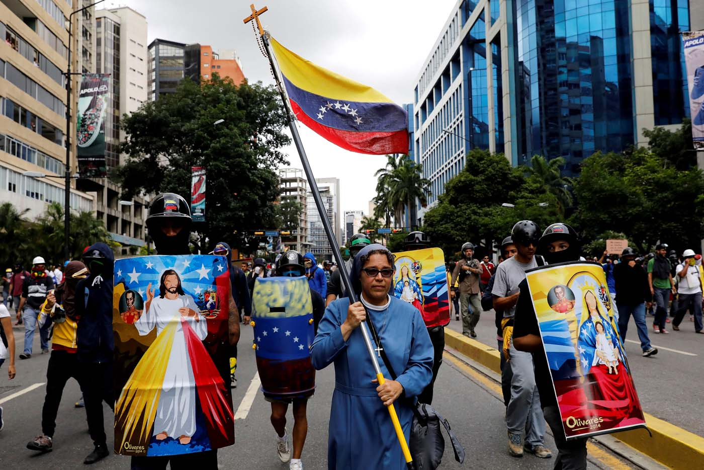 FILE PHOTO: A nun carries Venezuelan flag next to demonstrators carrying homemade shields with religious images, during a rally against Venezuelan President Nicolas Maduro's government in Caracas, Venezuela June 7, 2017. Picture taken June 7, 2017. REUTERS/Carlos Garcia Rawlins/File Photo