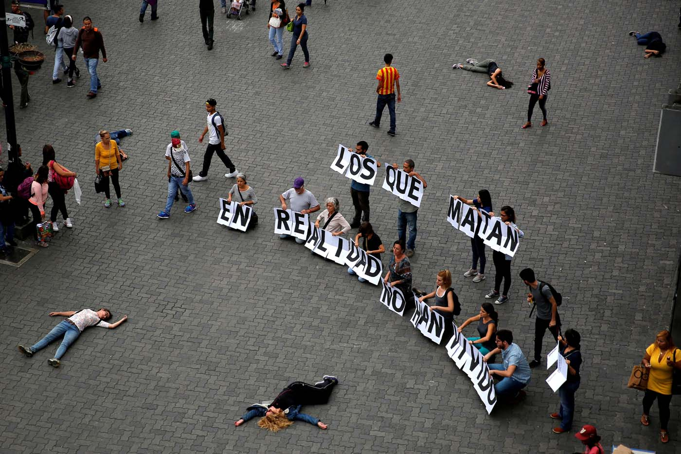 """Opposition supporters hold letters to build a banner that reads """"Those who kill in fact they have not lived"""" during a rally against Venezuelan President Nicolas Maduro's government in Caracas, Venezuela June 8, 2017. Picture taken June 8, 2017. REUTERS/Ivan Alvarado"""