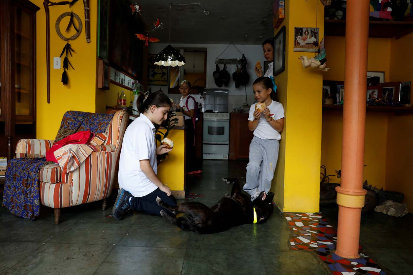 Eloisa Toro (L) and her sisters play with their dog after arriving from school on a day of protests in Caracas, Venezuela June 19, 2017. Picture taken June 19, 2017. REUTERS/Carlos Garcia Rawlins