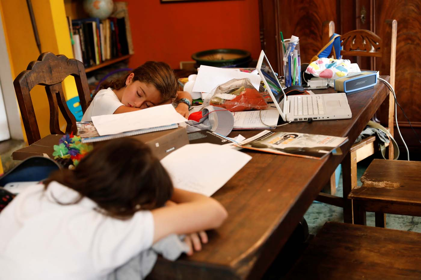 Carlota Valenzuela (L) and her sister Eloisa Toro, fall asleep on the table after arriving from school on a day of protests in Caracas, Venezuela June 7, 2017. Picture taken June 7, 2017. REUTERS/Carlos Garcia Rawlins