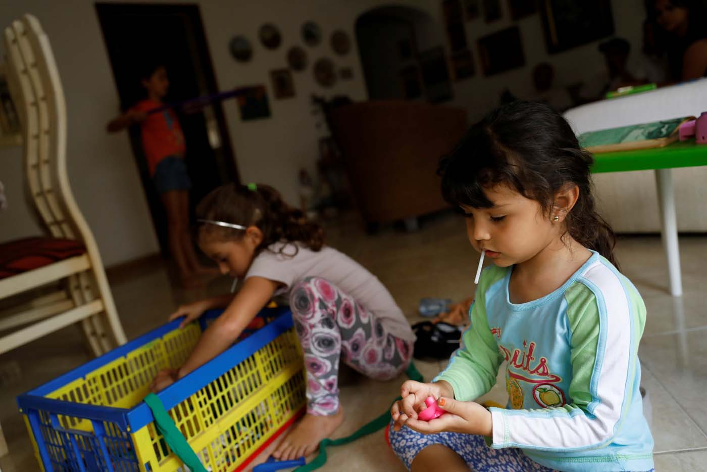 Renata Bonilla (R), plays with her cousins at their grandmother's house on a day of protests in Caracas, Venezuela June 14, 2017. Picture taken June 14, 2017. REUTERS/Carlos Garcia Rawlins