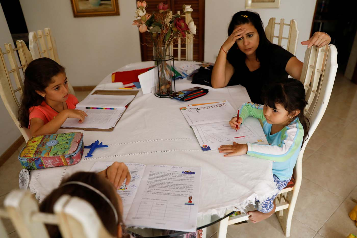 Aldrina Valenzuela (C), helps her daughter Renata (R) and her nieces Carlota (L) and Carmen, to do the homework at her mother's house on a day of protests in Caracas, Venezuela June 14, 2017. Picture taken June 14, 2017. REUTERS/Carlos Garcia Rawlins