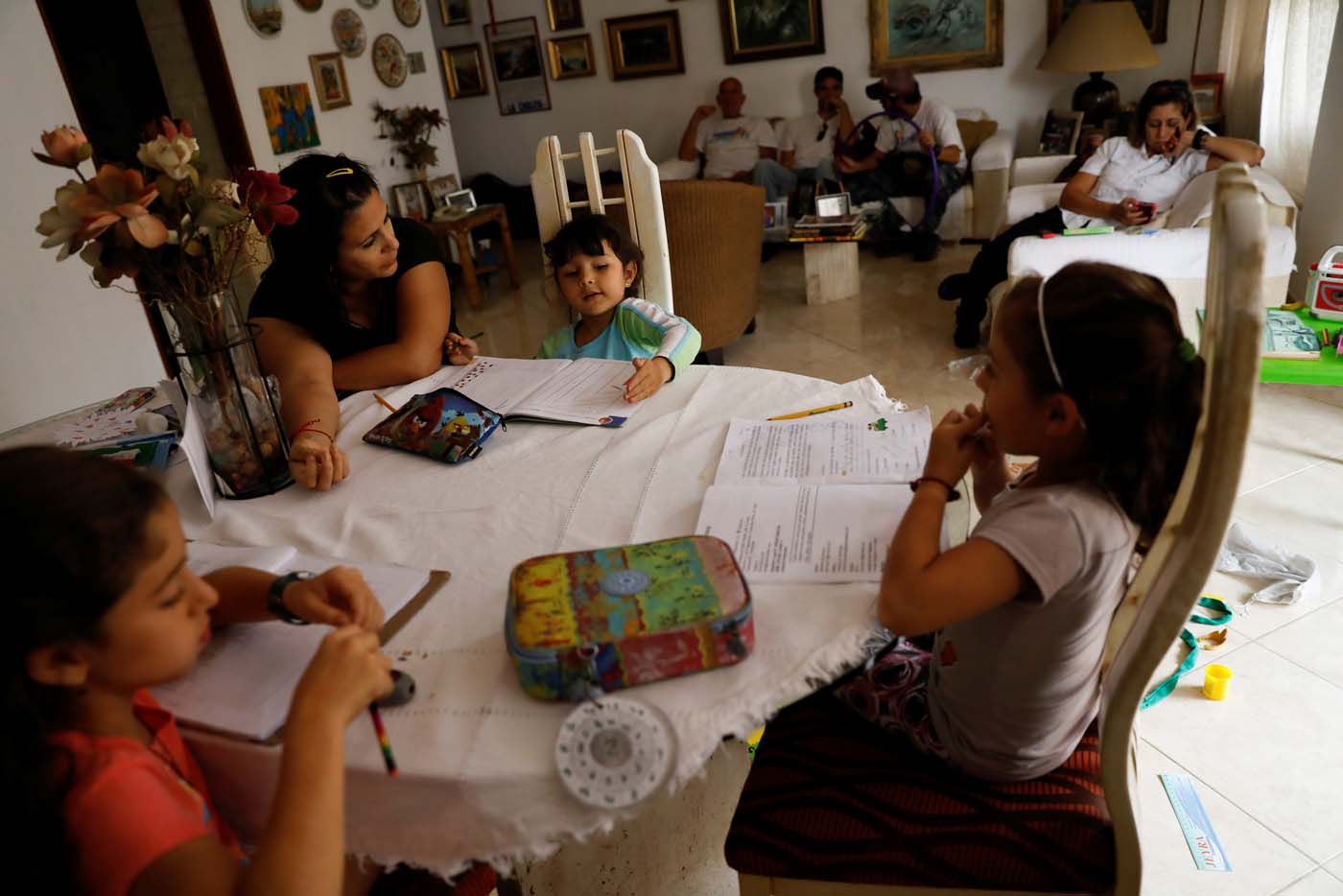 Aldrina Valenzuela (L), helps her daughter Renata (C) and her nieces Carlota (L) and Carmen, to do the homework at her mother's house on a day of protests in Caracas, Venezuela June 14, 2017. Picture taken June 14, 2017. REUTERS/Carlos Garcia Rawlins
