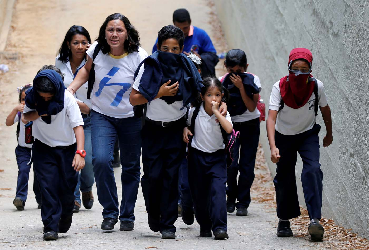 FILE PHOTO: School children protect themselves from tear gas during a rally against Venezuela's President Nicolas Maduro in Caracas, Venezuela April 26, 2017. REUTERS/Carlos Garcia Rawlins/File Photo