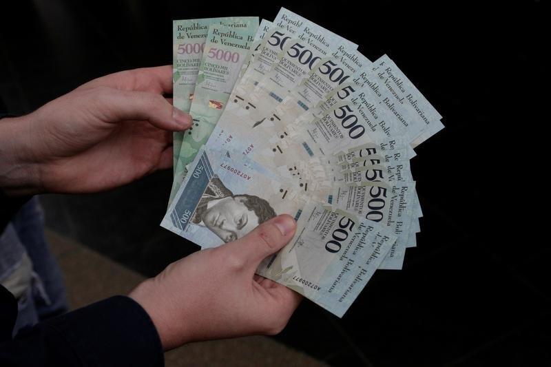 Una persona sosteniendo unos billetes de 500 y 5000 bolívares en Caracas, ene 16, 2017. La subasta de divisas bajo el nuevo sistema cambiario de Venezuela, conocido como Dicom, arrojó un tipo de cambio de 2.640 bolívares por dólar, dijo el miércoles el Banco Central, lo que supone una devaluación del 16,6 por ciento respecto a la tasa de la semana pasada.  REUTERS/Marco Bello